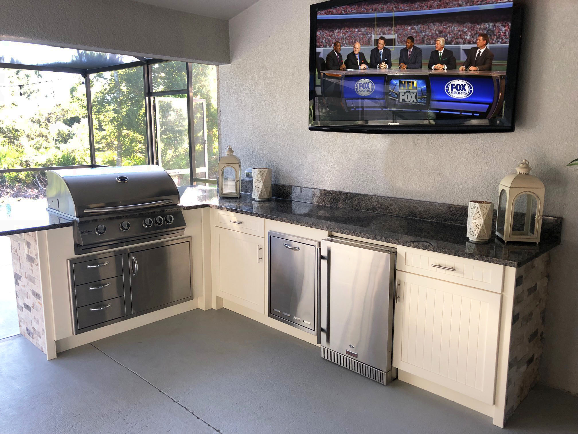 L shaped outdoor kitchen with grill and mini fridge